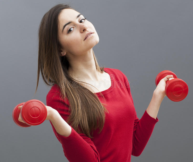 Relaxed 20s office girl holding dumb bells for toned arms and wellness stock image