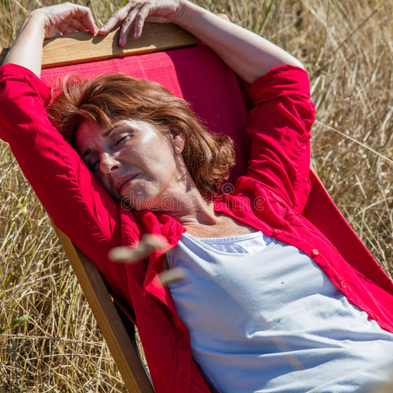 Relaxed 50s woman enjoying sun warmth on her deckchair. Sun warmth wellbeing - sleeping mature woman enjoying sunbathing on deckchair,closing eyes in summer stock photography