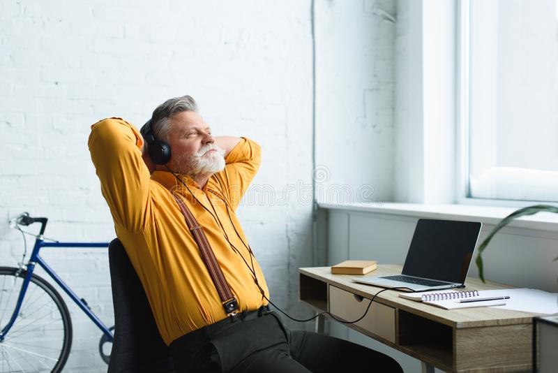relaxed senior man in headphones resting with hands behind head and looking away while using laptop with blank screen royalty free stock images