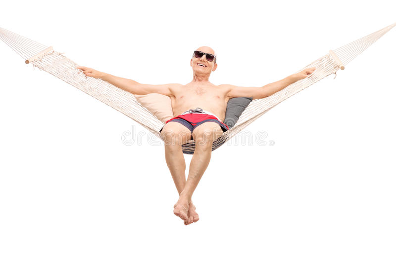 Relaxed senior man lying on a hammock. Relaxed senior man in red swim trunks lying on a comfortable hammock isolated on white background stock photography