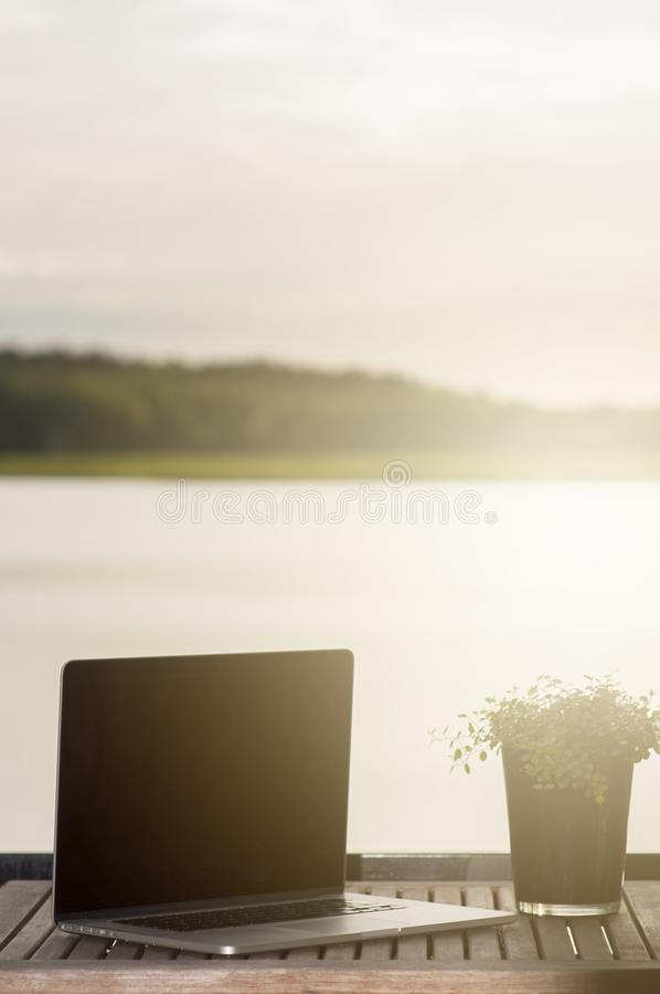 A relaxed and sentimental scene on a balcony with a laptop and a plant on a wooden terrace table, near ocean in archipelago in. Porvoo Finland royalty free stock images