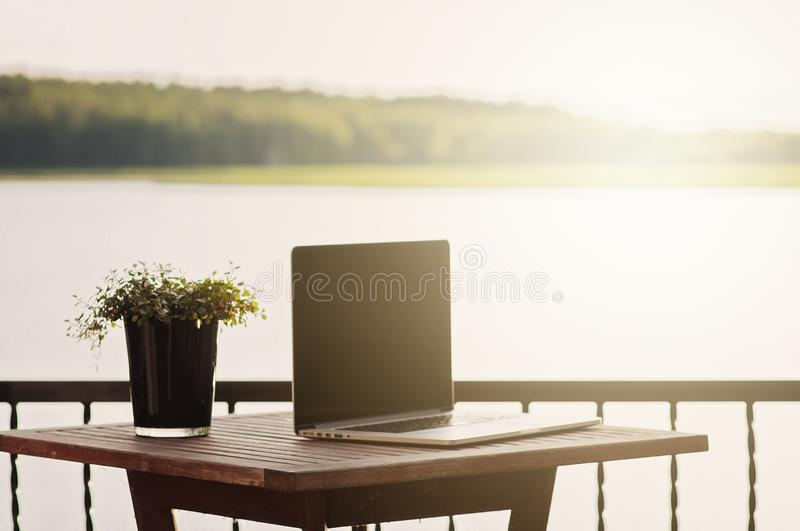 A relaxed and sentimental scene on a balcony with a laptop and a plant on a wooden terrace table, near ocean in archipelago in royalty free stock photography