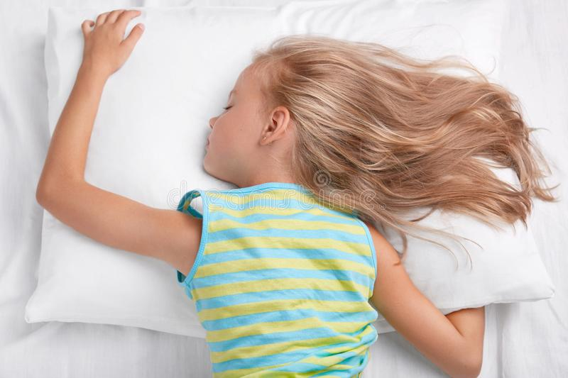 Relaxed small child lies on stomach, lies on soft pillow, being deep in sleep, lies on white pillow, has light straight hair, enjo royalty free stock photography