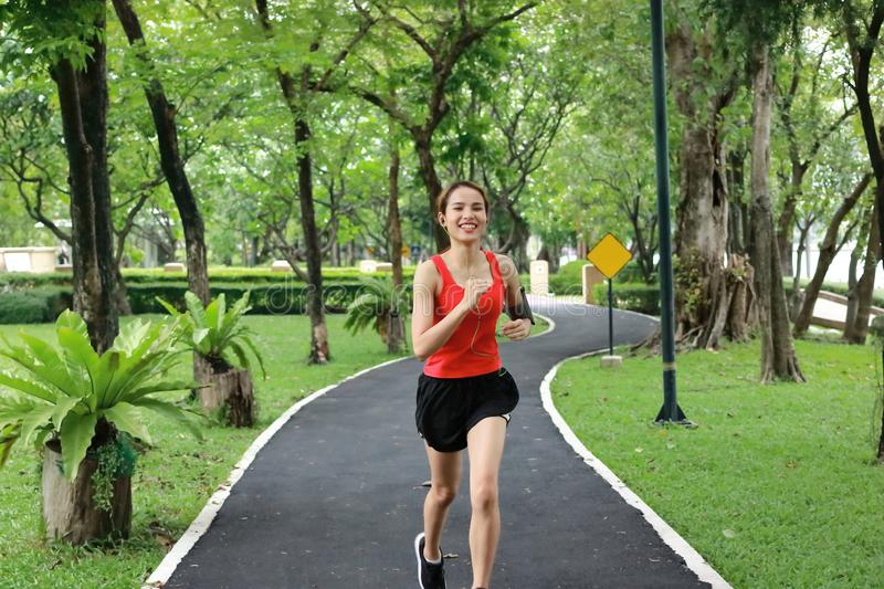 Relaxed smiling Asian fitness runner woman listening music and running workout in natural park stock images