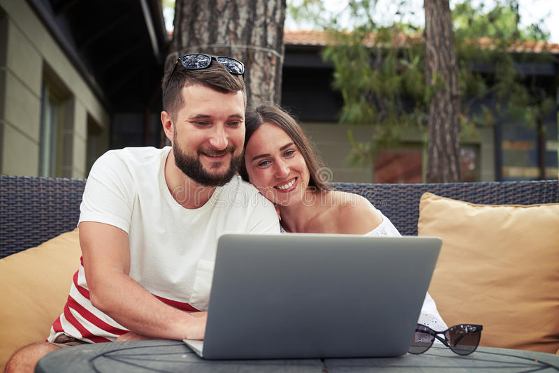Relaxed smiling couple on terrace is watching something on laptop stock image