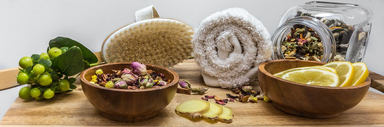 Relaxed SPA setting with herbal tea and brush. Lifestyle setting for SPA, healthy lifestyle with herbal tea lemon ginger and brush on wooden board royalty free stock images