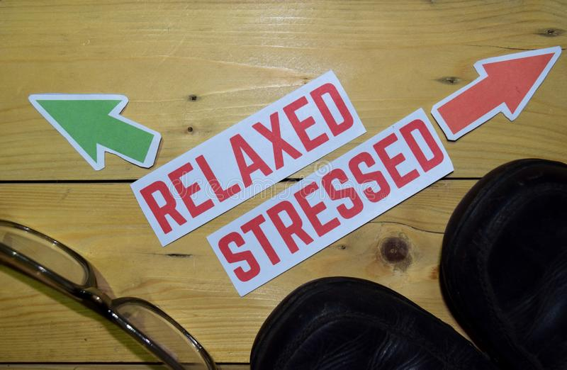 Relaxed or Stressed opposite direction signs with boots and eyeglasses on wooden. Vintage background. Business, education, finance and concepts royalty free stock images