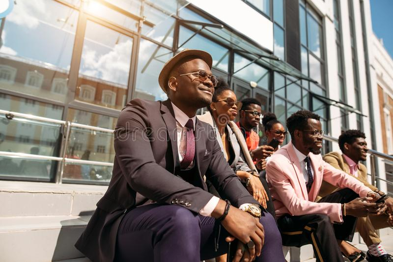 Relaxed stylish people with optimistic faces. Young african hopefuls. side shot. people anf fashion idea royalty free stock images