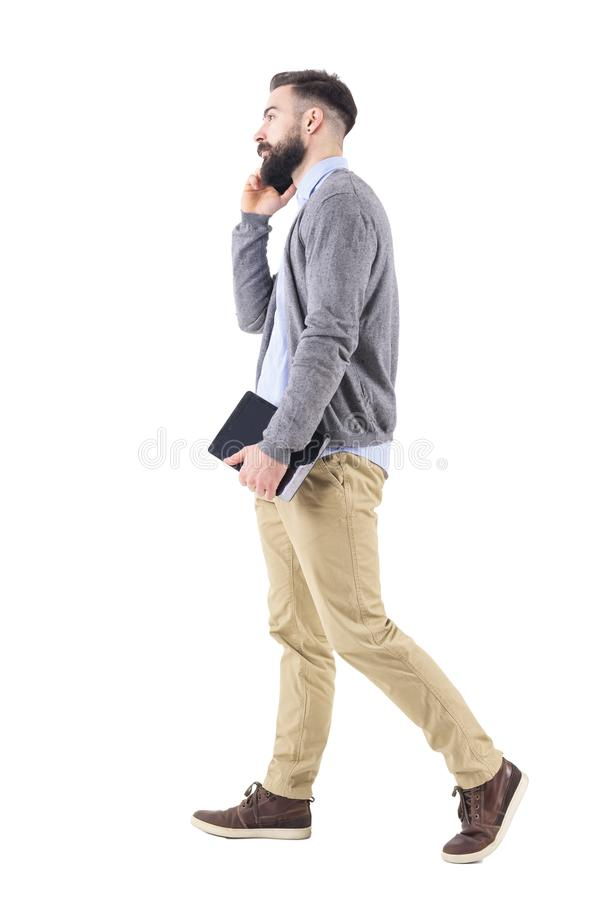Relaxed successful businessman on the phone walking and carrying tablet computer. Full body length portrait isolated on white studio background stock photography