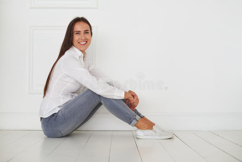 Relaxed and sunny female is sitting on the floor stock photography