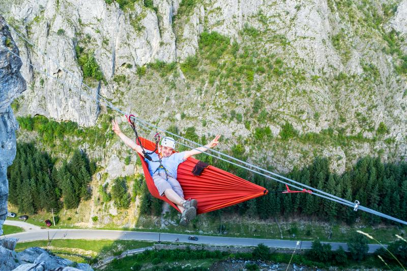 Relaxed tourist male in a hammock high up in a mountain, above the valley, secured with a via ferrata set on two steel wires stock photos