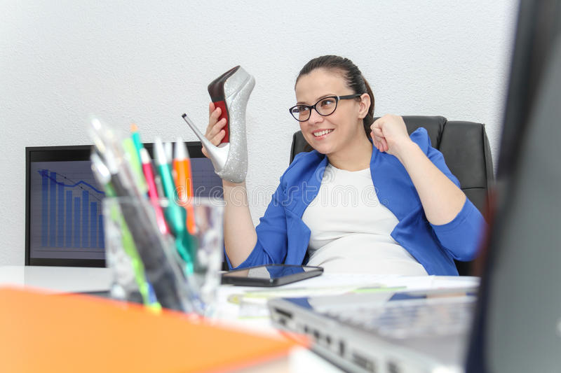 Relaxed and winning business woman sitting with her legs on desk royalty free stock photos