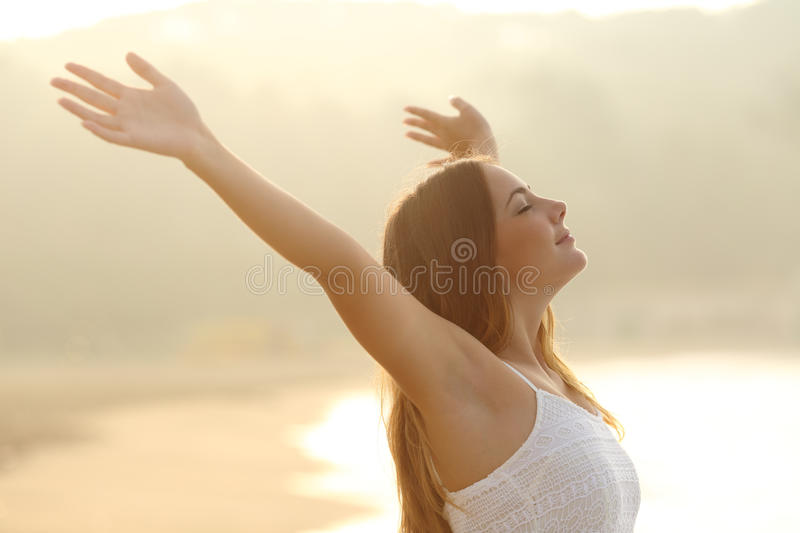 Relaxed woman breathing fresh air raising arms at sunrise royalty free stock image