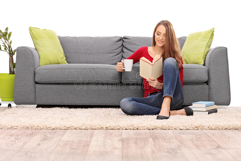 Relaxed woman enjoying a coffee and reading a book stock images