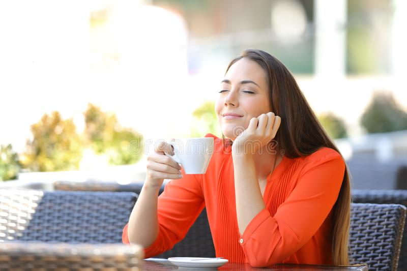 Relaxed woman enjoying smelling coffee in a bar royalty free stock images