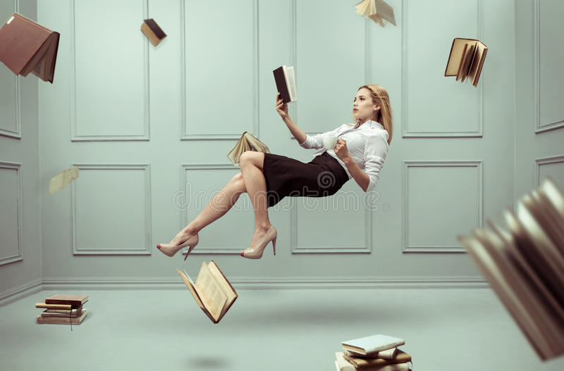A relaxed woman levitates in a room stock photos