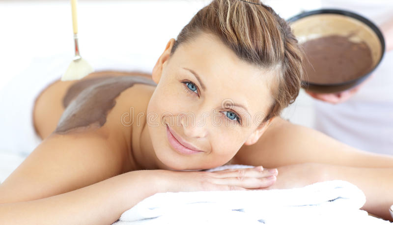 Relaxed woman liking a mud skin treatment. In a Spa center stock images