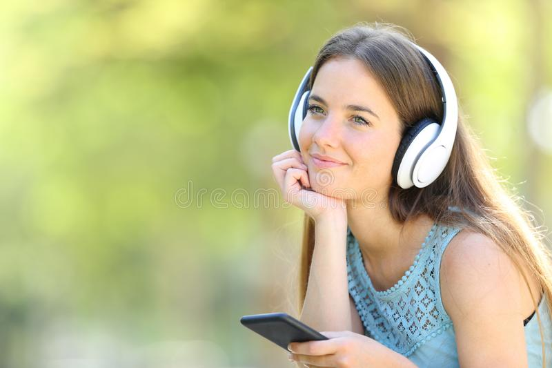Relaxed woman listening to music looking away. Relaxed woman listening to music holding smart phone and looking away in a park with a green background royalty free stock image