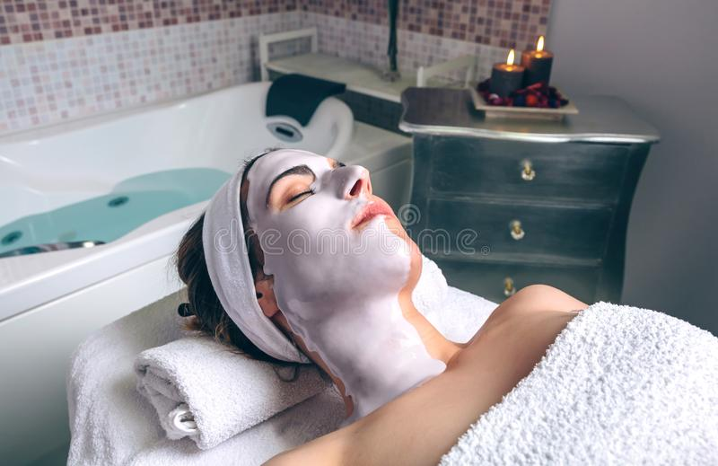 Relaxed woman lying with facial mask in spa stock photo