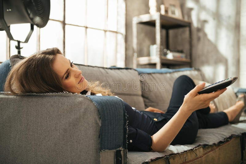 Relaxed woman lying on sofa and watching tv in loft apartment. Relaxed young brunette woman lying on sofa and watching tv in loft apartment. Urban chic loft stock image