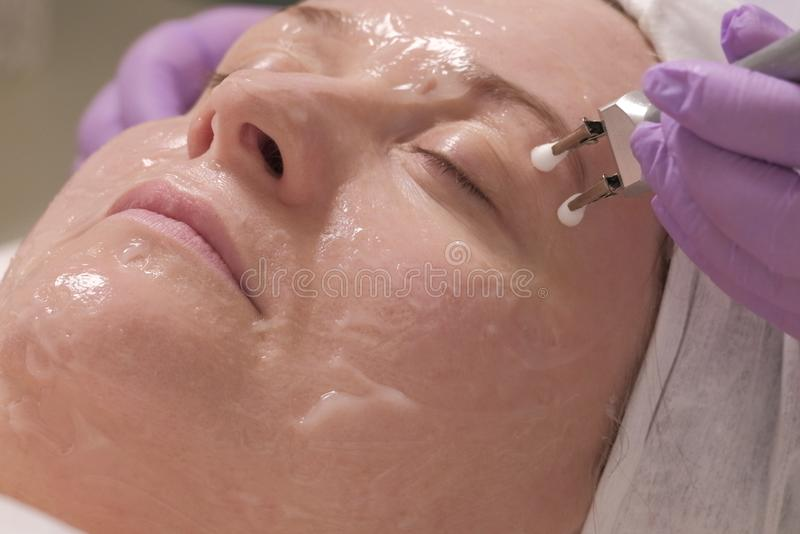 Relaxed woman on microcurrent cosmetological procedure. The hands of a beautician remove wrinkles around the eyes of a middle-aged. Relaxed woman with eyes royalty free stock images