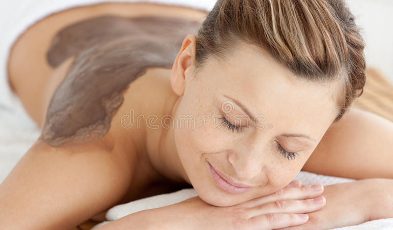 Relaxed woman during a mud treatment stock photos
