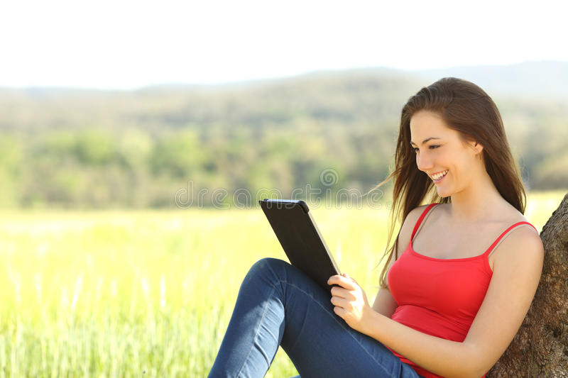 Relaxed woman reading an ebook in the country. Leaning under a tree shadow wearing a red color shirt stock image
