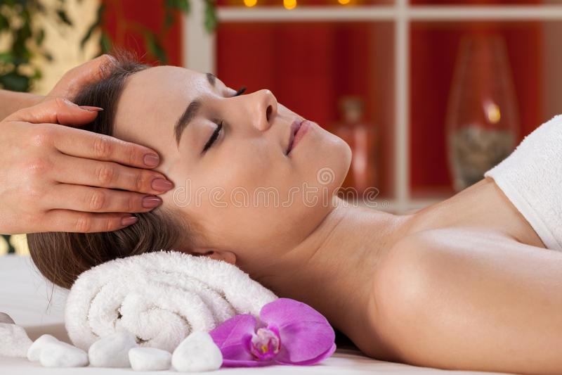 Relaxed woman receiving head massage stock photo