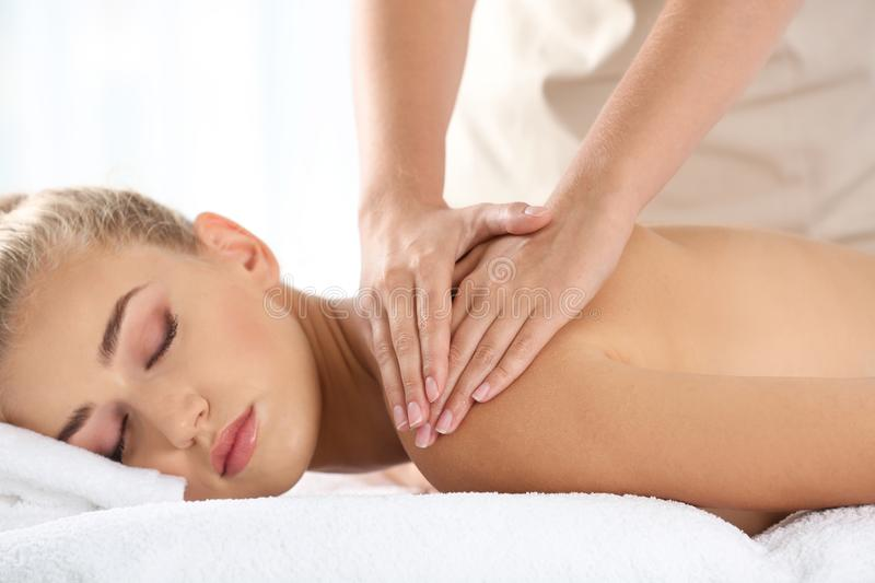 Relaxed woman receiving shoulders massage stock image