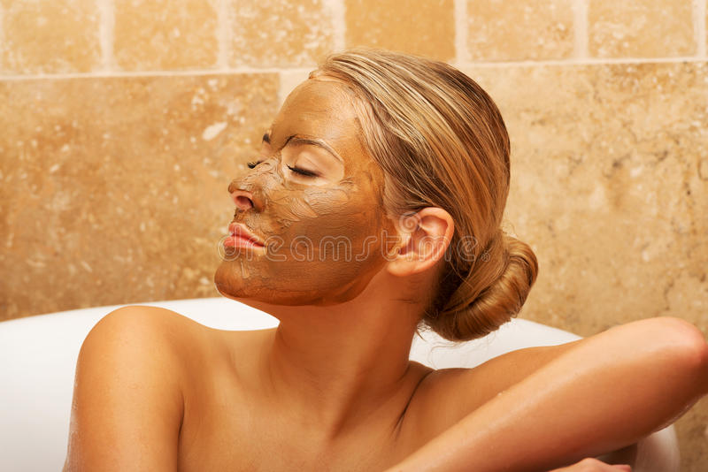 Relaxed woman sitting in a bath with closed eyes stock images
