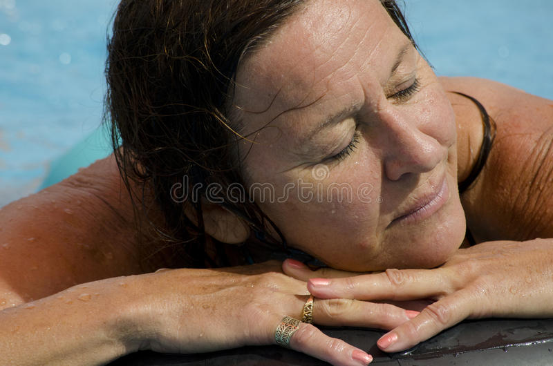 Relaxed woman in swimming pool royalty free stock photo