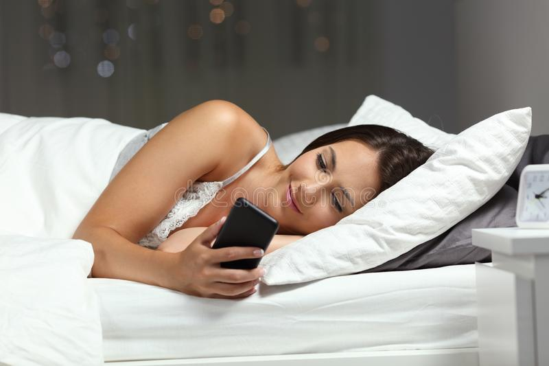 Woman using a smart phone in the night on a bed at home royalty free stock photography