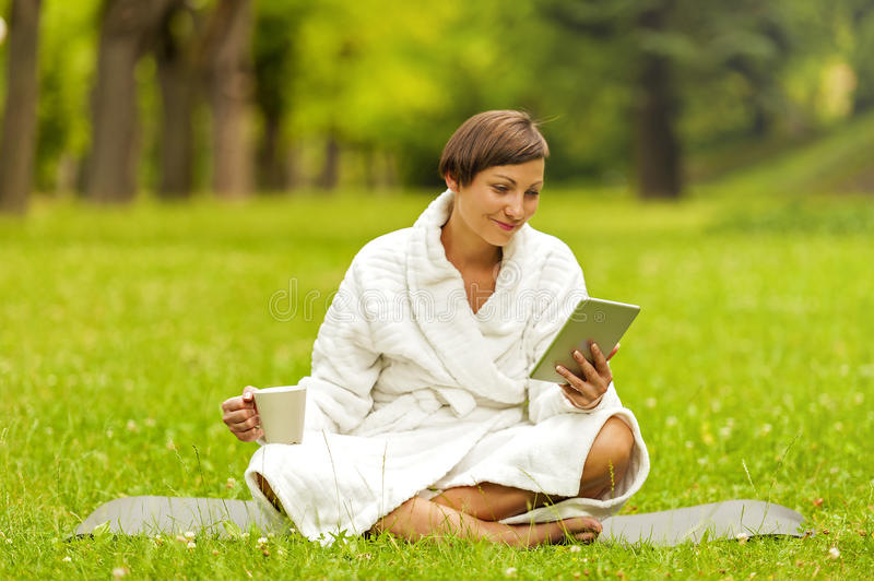Relaxed woman using tablet, siting on the green grass in bathrobe. stock photo