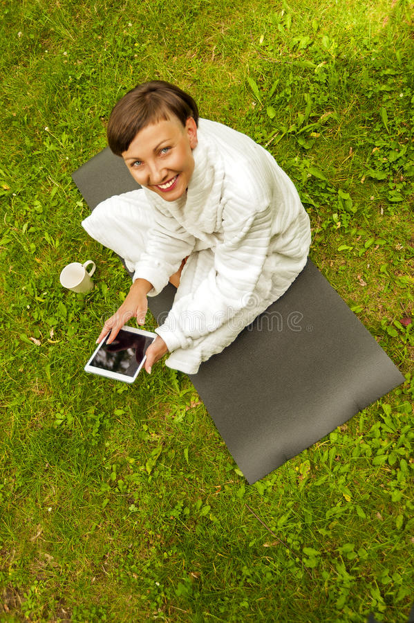 Relaxed woman using tablet, siting on the green grass in bathrobe. stock photos