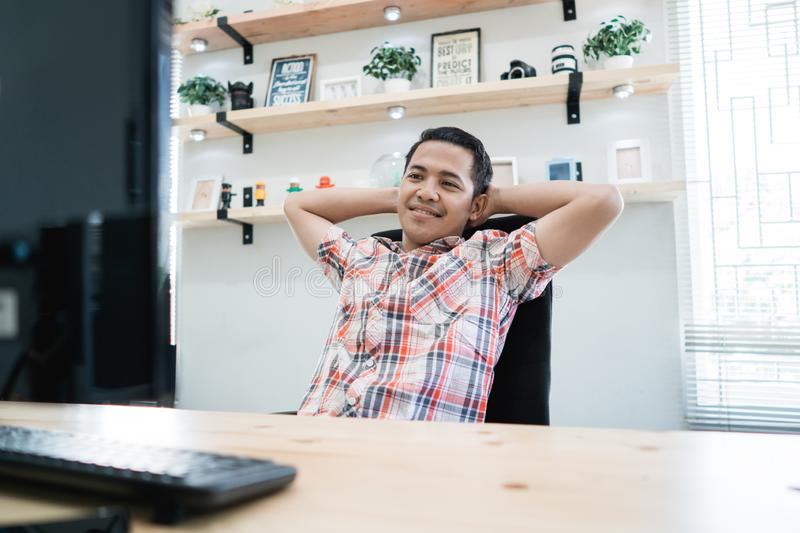Relaxed worker laying on his chair while working. In the office royalty free stock image