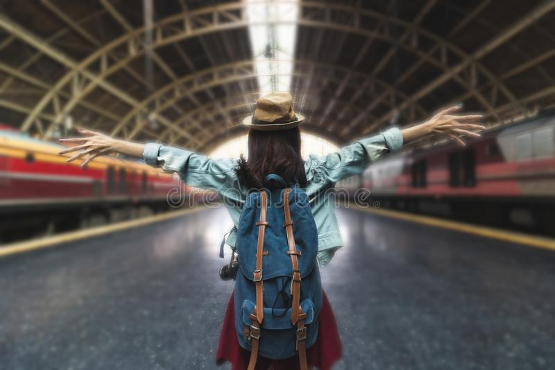 Relaxed young Asian backpacker female standing at train station. Travel lifestyle concept royalty free stock photo