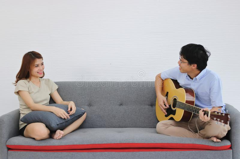 Relaxed young Asian couple playing acoustic guitar together in living room. Love and romance people concept stock photos