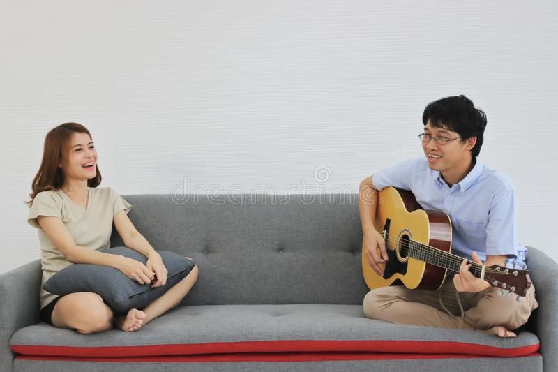 Relaxed young Asian couple playing acoustic guitar together in living room. Love and romance people concept stock photo