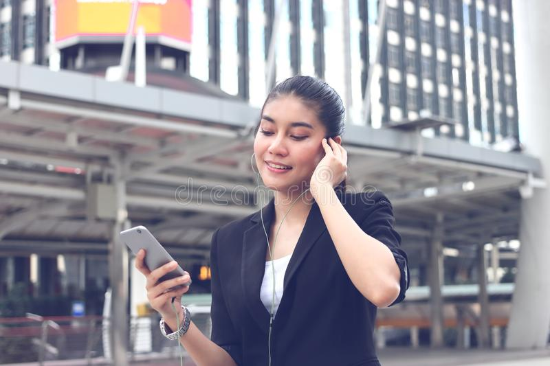 Relaxed young Asian woman listening music with mobile smart phone in urban city stock photo