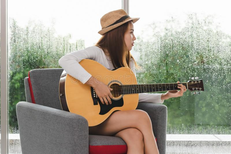 Relaxed young Asian woman playing acoustic guitar in living room stock photography