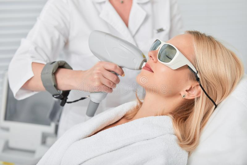 Relaxed young blonde client receiving hair removal laser epilation. Close up side view photo royalty free stock photography