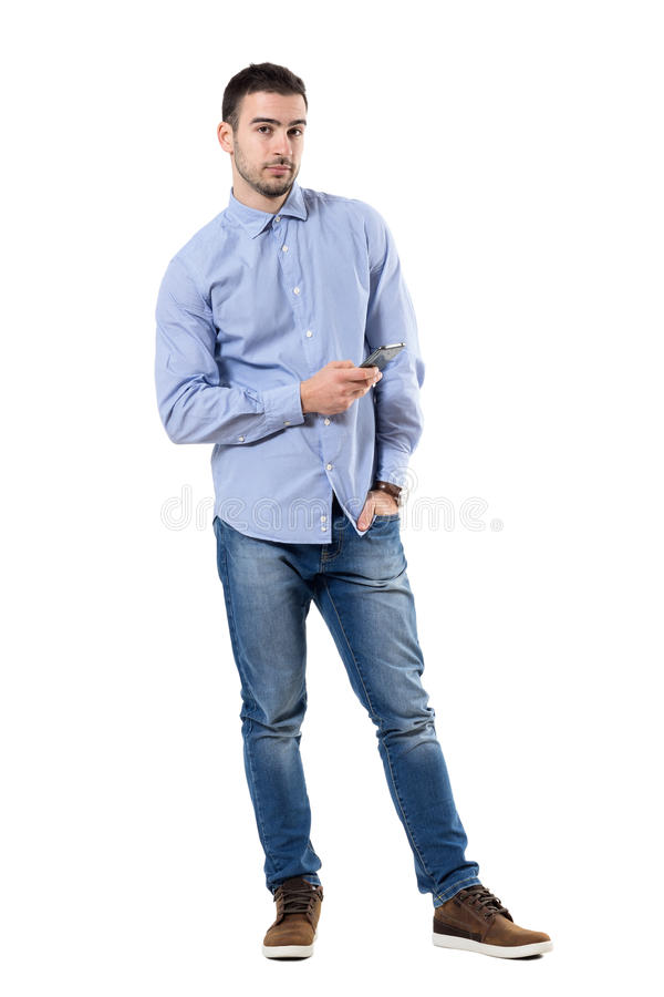 Relaxed young corporate man holding mobile phone looking at camera. stock photos