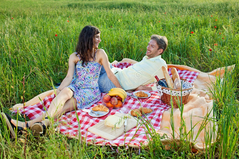 Relaxed young couple enjoying a summer picnic. Relaxed young couple enjoying a summer picnic as they sit smiling and chatting on a red and w.hite checked rug in stock photos