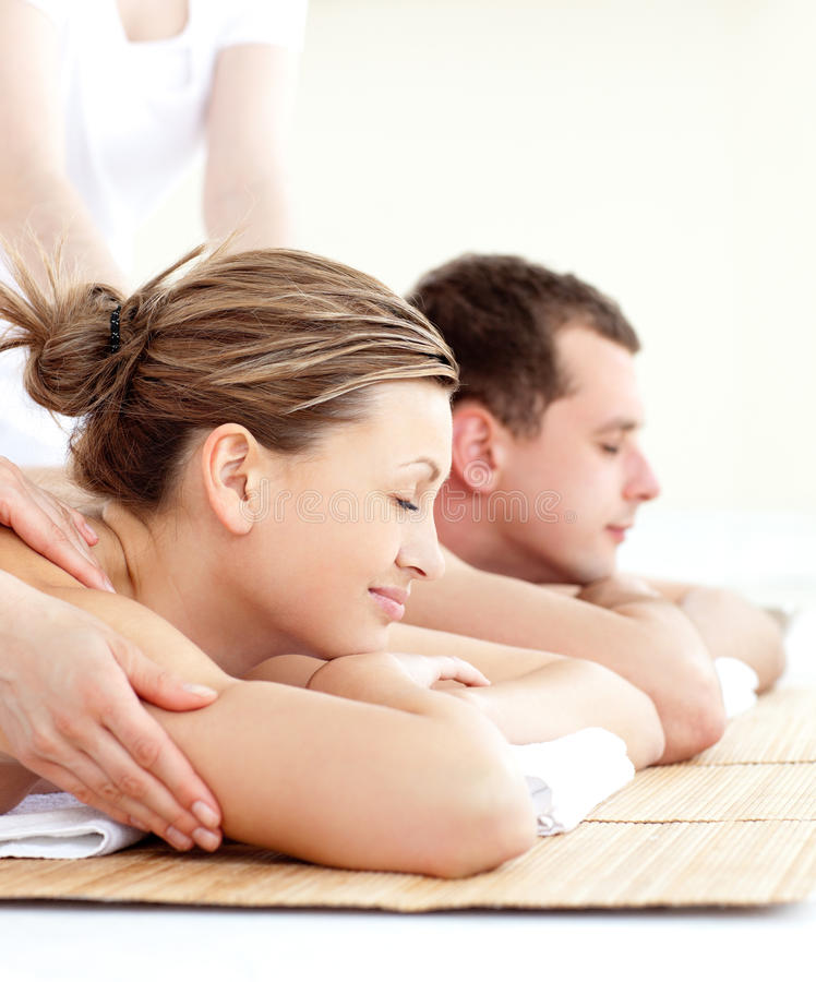 Relaxed young couple receiving a back massage. In a spa center stock image
