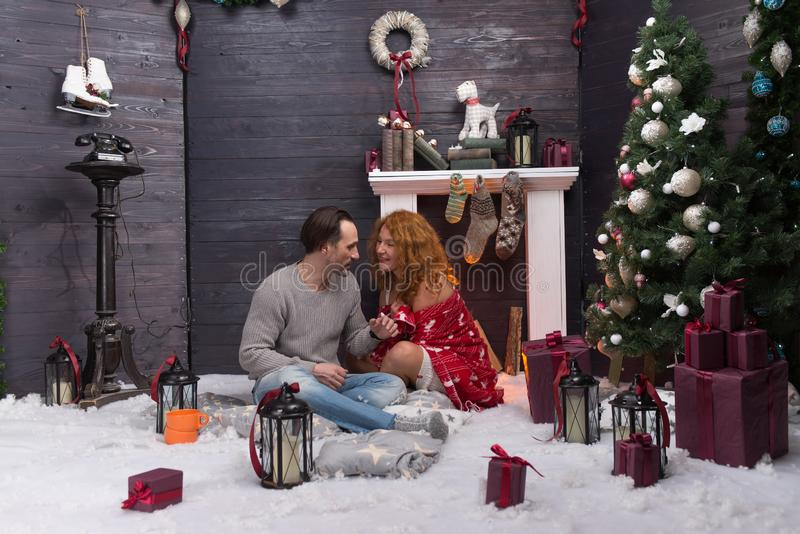 Calm man talking to his happy wife while sitting near the fireplace. Relaxed young couple sitting in New Year decorated interior and talking while spending time stock images