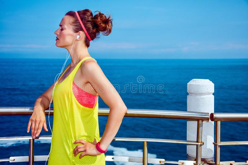 Relaxed young fitness woman listening to music at embankment stock images