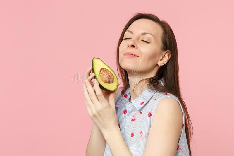 Relaxed young girl in summer clothes keeping eyes clothes hold fresh ripe avocado fruit isolated on pink pastel stock photo