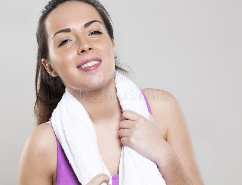 Relaxed young gym girl relaxing with fitness towel on royalty free stock photo