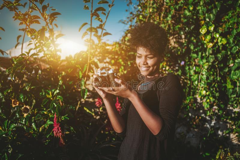 Black young female with retro film camera. Relaxed young lovely Brazilian girl with African curly hair is staying in a garden in front of green fence and taking royalty free stock photos