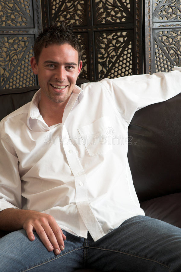Relaxed young man. Relaxed young adult male wearing blue jeans, a loose white cotton shirt and sitting comfortable on a leather couch stock images